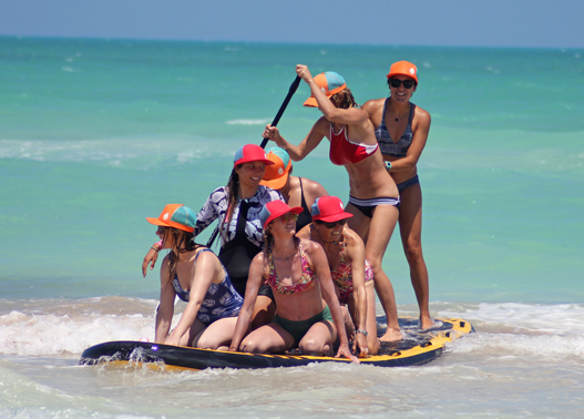 Girls SUPing with Sensi Bikinis and Buoy Wear's floating hat